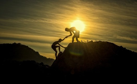 Symbolizing teamwork, one boy helps another navigate a rocky ledge -- all in silhouette against a setting sun.