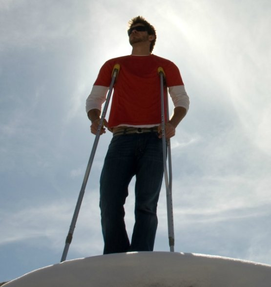 Man on mountain with crutches against blue sky.