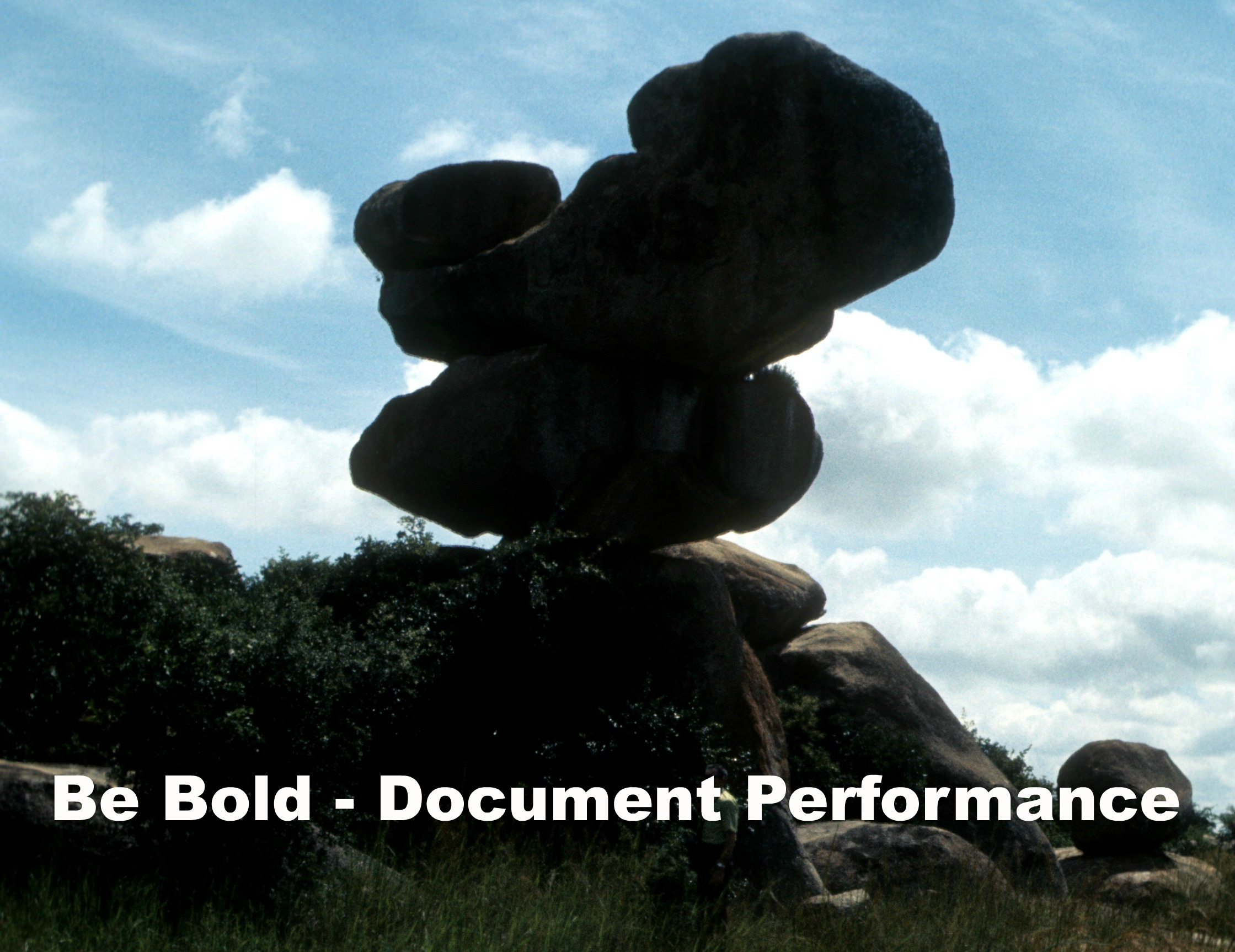 teetering rock formation with caption