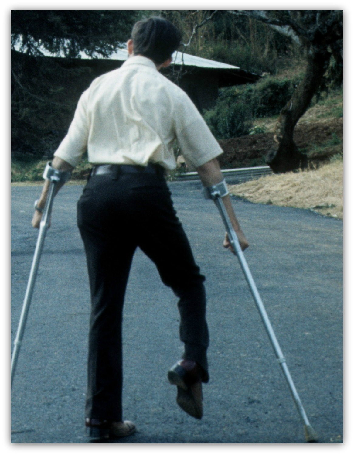 Jim Hasse (from backside) walking up hill with Canadian crutches.