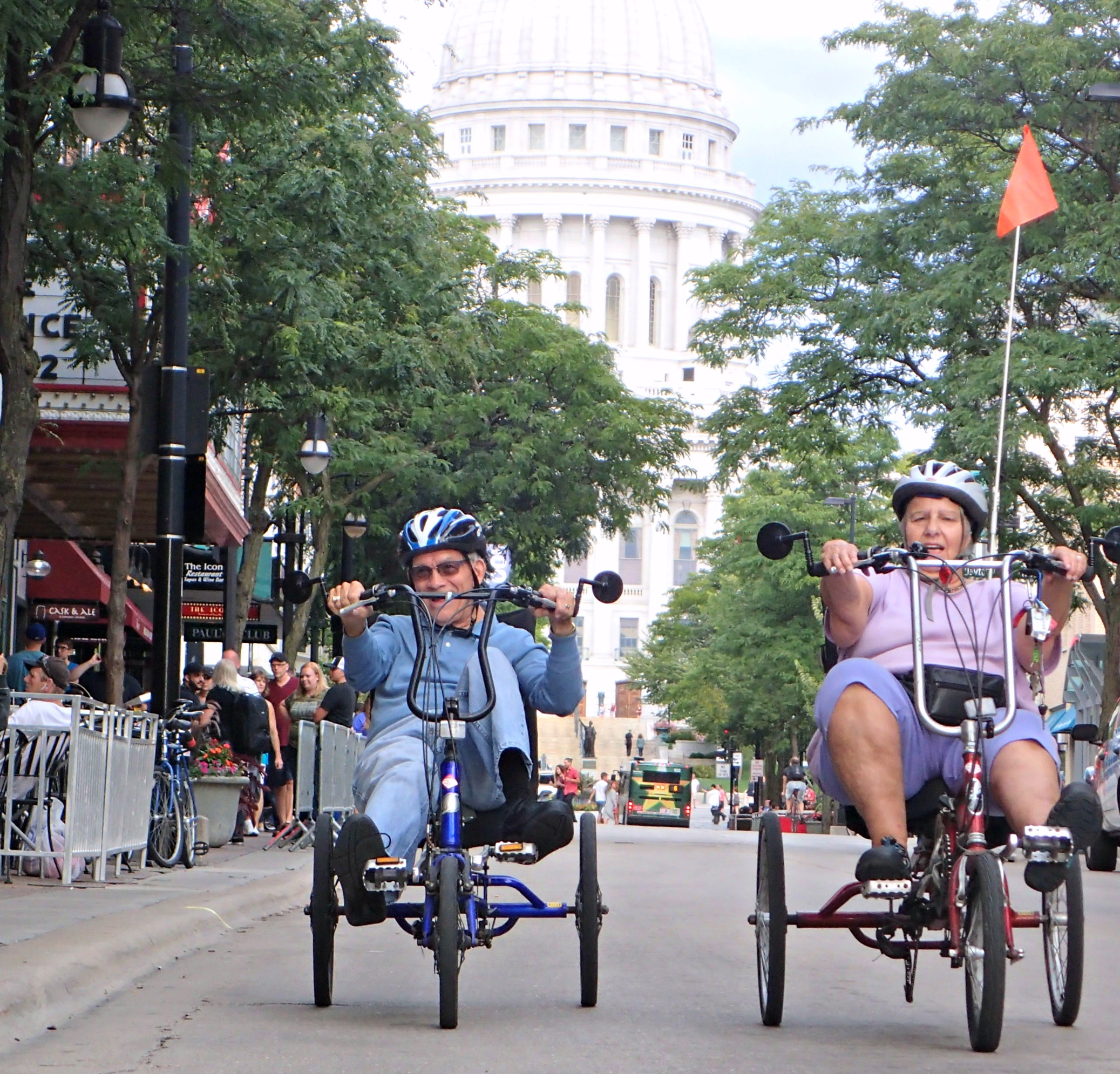 Pam and Jim riding recumbent tricycles down State St. in Madison, WI.