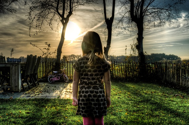 Girl in backyard at sunset.