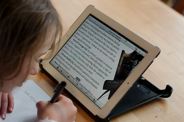 Motivated Kids: Elementary girl taking notes from iPad.