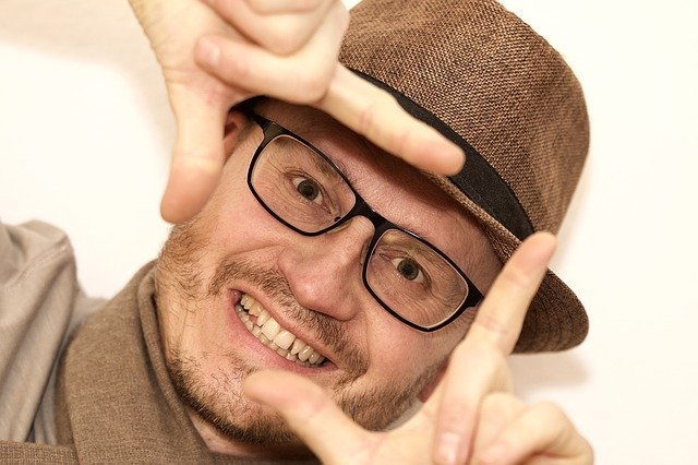 Tight shot of man who is forming a square frame with his thumbs and forefingers, illustrating communication skill builders.