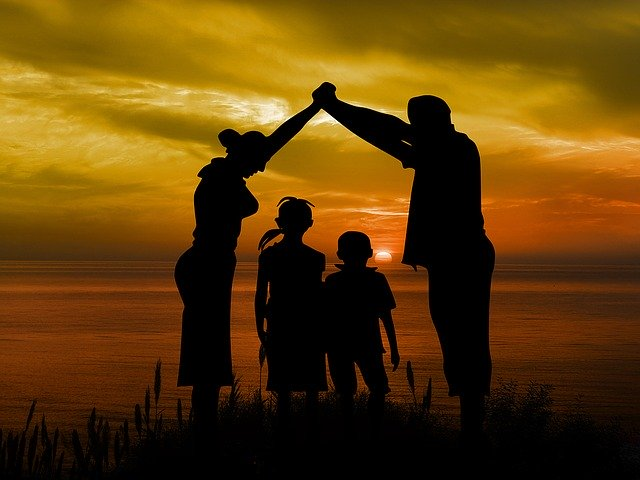 Mom, dad and two children together at sunset.