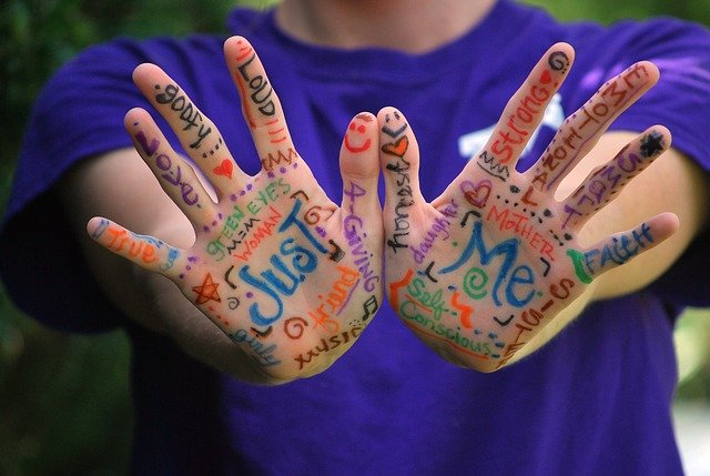 Two palms of youngster painted with colorful hand-written notes.